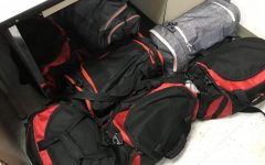 Pile of gym bags in a classroom that should be in the locker room
